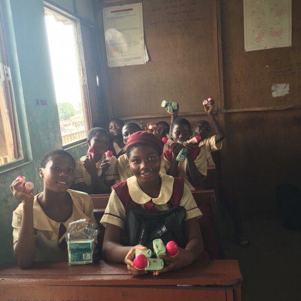 Happy students in their classroom receiving the donated products from Unilever Nigeria