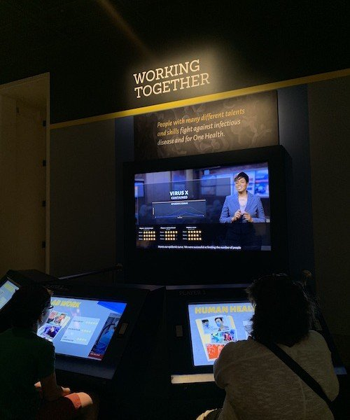 People playing a game at the Smithsonian's Outbreak: Epidemics in a Connected World Exhibition