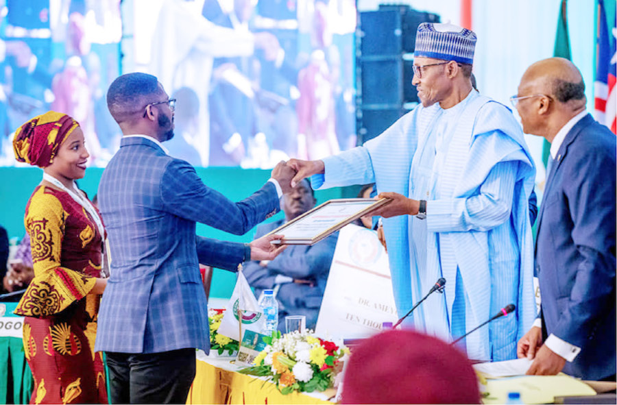 Bankole Cardoso and Niniola Soleye accepting award from President Muhammadu Buhari