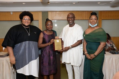Dolapo Osuntuyi collecting the Social Impact Award for the Dolly Children Foundation